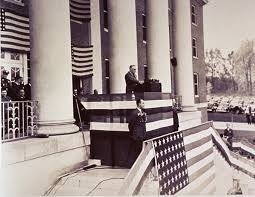 Franklin Delanor Roosevelt speaking before a crowd on the steps of the NIH. A broom lies against a large pillar, near the podium.