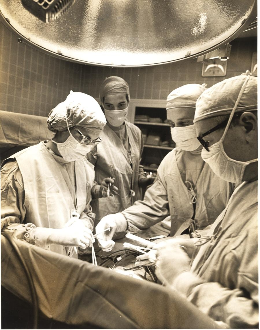 black and white photo of surgeons who are conducting open heart surgery on a patient