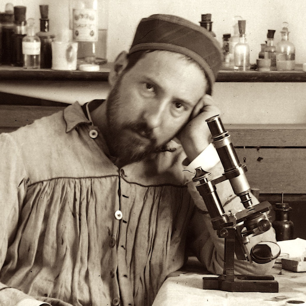 Photograph of Santiago Ramón y Cajal sitting at his drawing table with a microscope printed large on exhibit