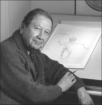 Photograph of Howard Bartner in front of his drawing board