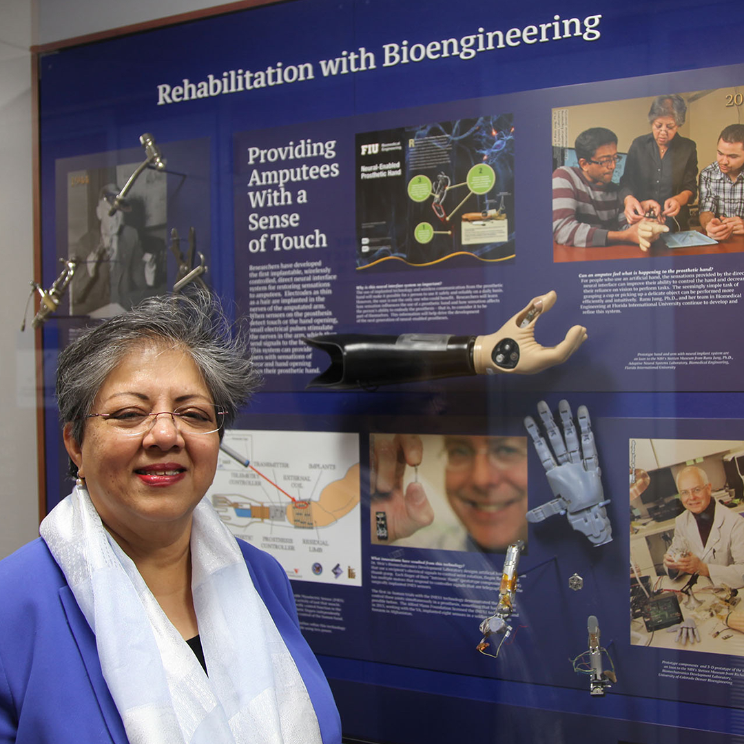 A woman is standing in front of the exhibit titled Rehabilitation with Bioengineering, which displays prosthetic devices, images and text