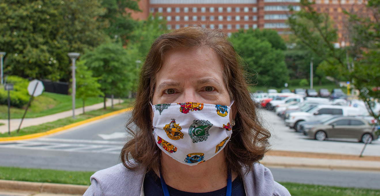 An NIH Employee wearing a Mask to prevent COVID-19 Spread, standing in front of the NIH Clinical Center on Campus